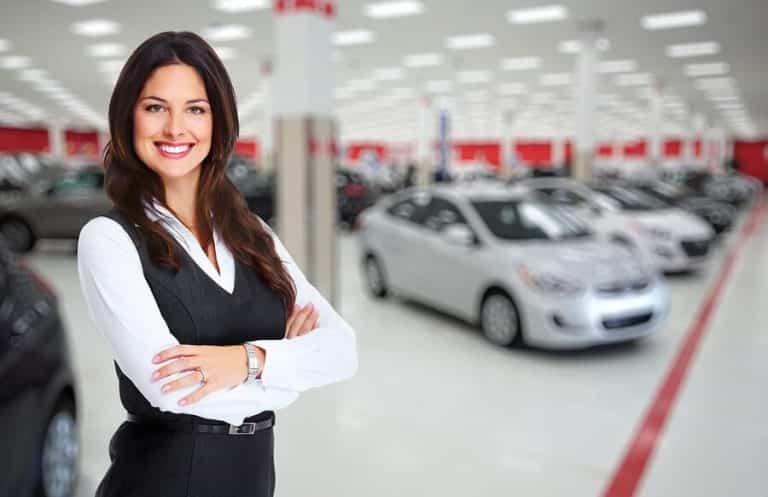 Happy saleswoman at a car dealership